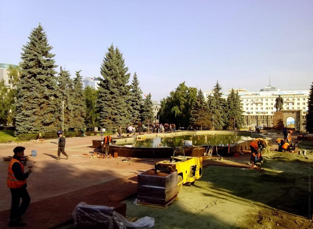 Укладка тротуарной плитки вокруг фонтана на площади Революции в Челябинске